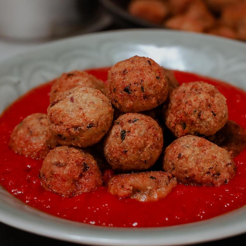 Des boulettes de légumineuses servies sur un fond de sauce tomate.