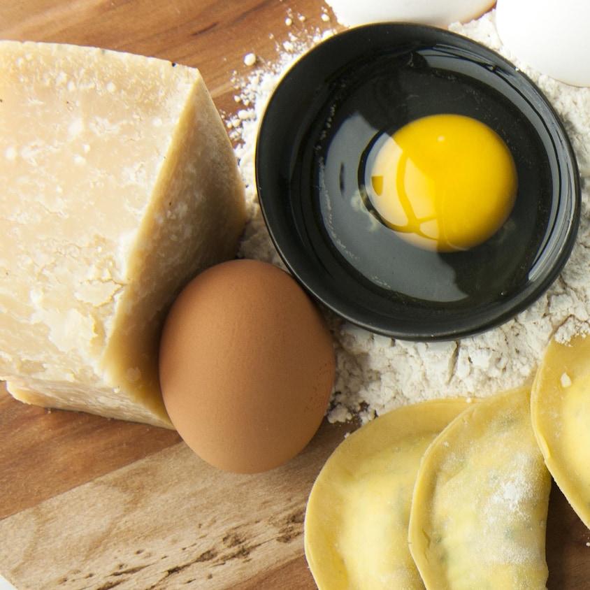Les ingrédients nécessaires à la préparation de pâtes fraîches, présentés sur une planche de bois: oeufs, farine et fromage, avec quelques pâtes fraîches.