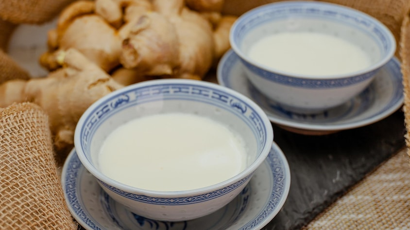 Deux bols avec du pouding au lait et au gingembre sont disposés sur une table.