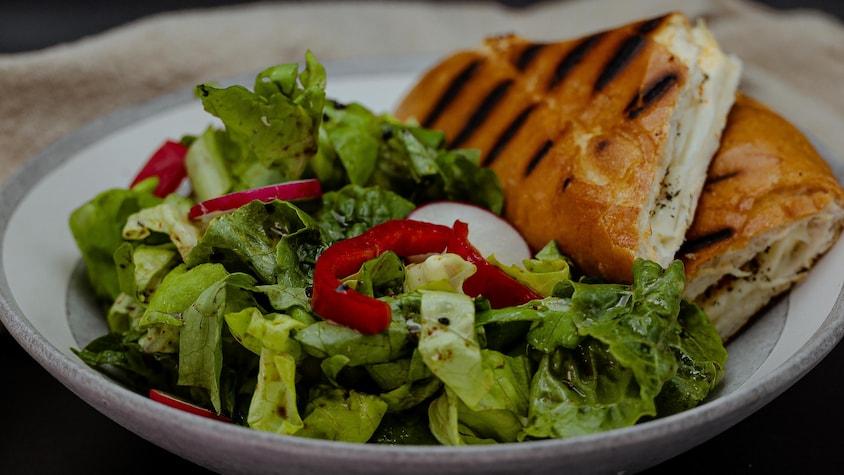 Deux parts de grilled cheese sont disposées dans une assiette à côté d'une salade.
