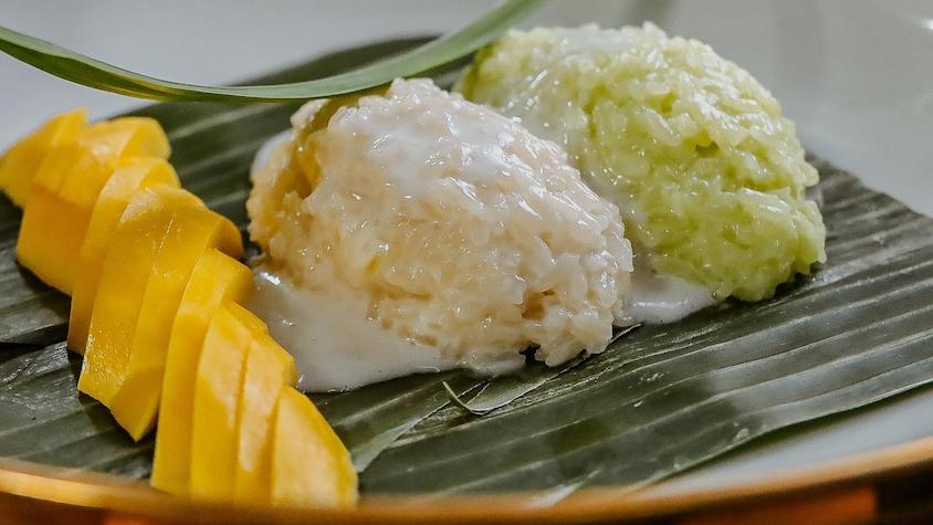 Deux boules de riz sont disposées dans une assiette à côté d'une mangue tranchée.