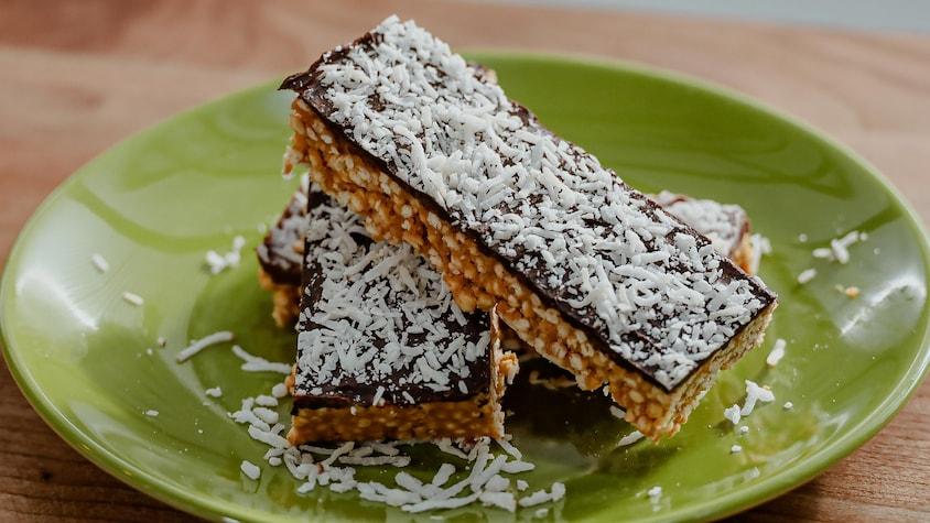 Des barres au chocolat et au quinoa soufflé servies sur une assiette verte.