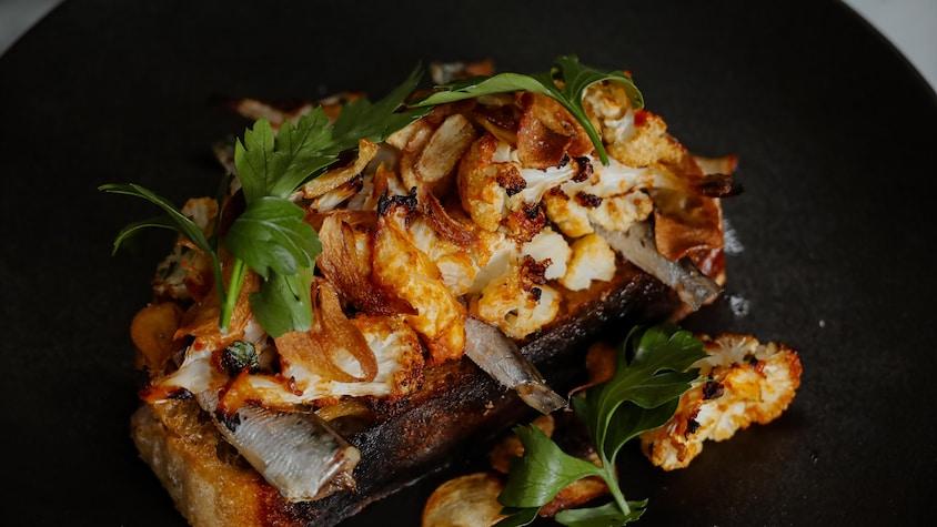 Une assiette de bruschetta au chou-fleur rôti et aux sardines.