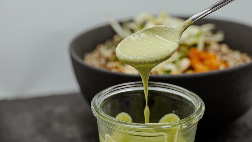 On prend une cuillérée de vinaigrette au tahini et à la coriandre.