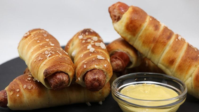 Des saucisses à hot dog enroulées de pâte cuite à côté d'un petit ramequin de sauce.