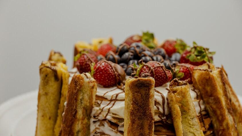 Gâteau blanc entouré de crêpes roulées et nappé de ftuits de saison et de coulis chocolat.
