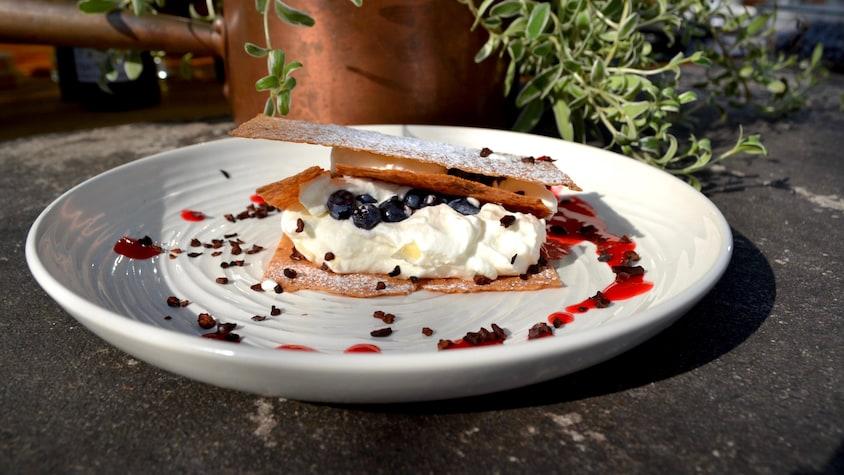 Millefeuille léger aux bleuets, crème et Grand Marnier dans une très grande assiette blanche.