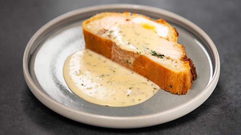 Un koulibiac servi dans une assiette ronde, (feuilleté de saumon) nappé d'une sauce au vin blanc aromatisée aux fines herbes.