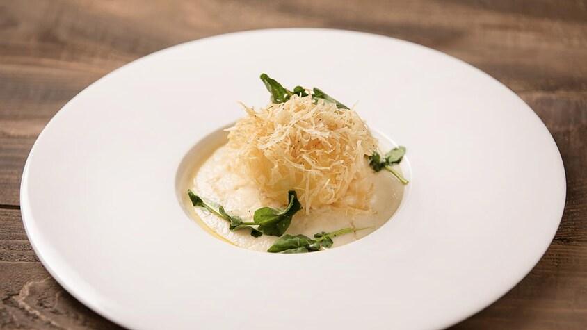 Une grande assiette avec au centre un œuf croustillant et lait d'oignon et salsifis.