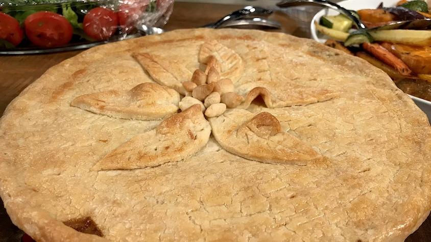 Une tourtière bien dorée et décorée de feuilles en pâte au centre.