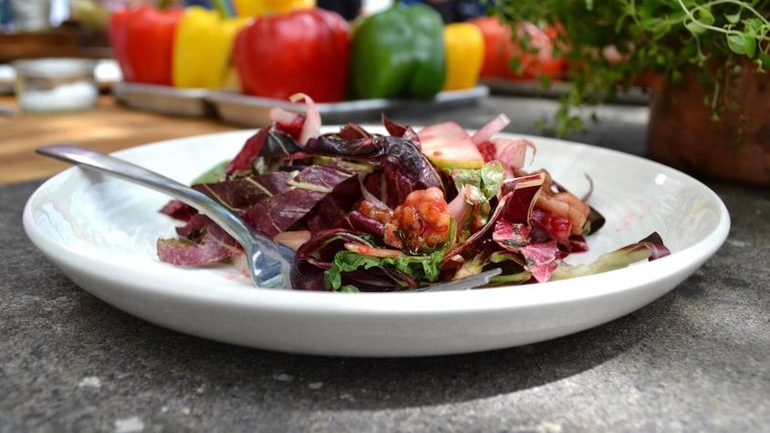 Salade de laitues amères et framboises servie dans une assiette blanche.