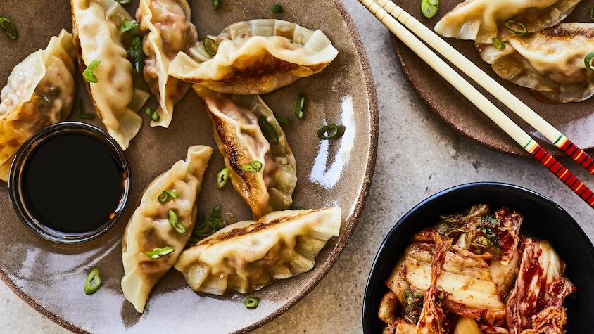 Une demi-douzaine de dumplings sont dans une grande assiette à côté d'un petit bol de sauce.
