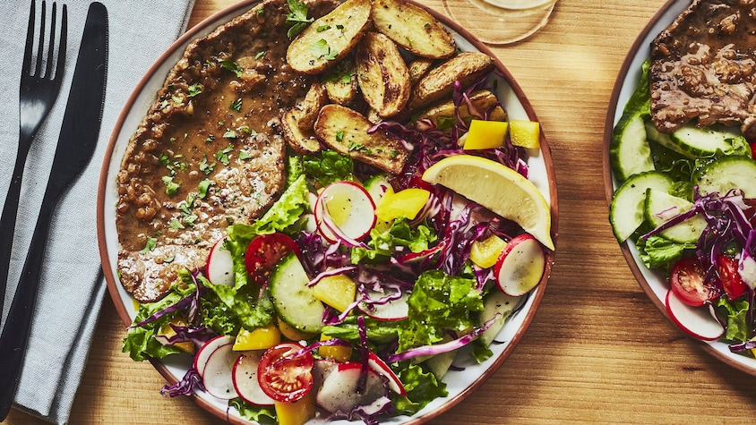 Une assiette d'escalope, accompagnée d'une salade et de patates, est sur la table.