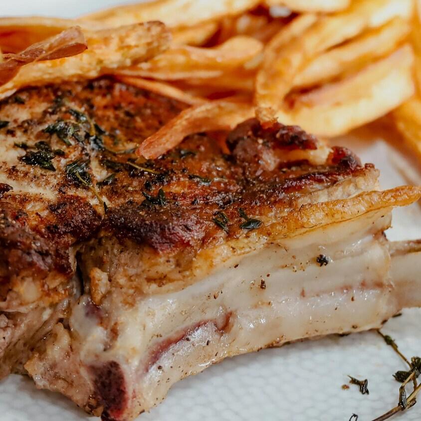 Une assiette de côte de veau servie avec des frites de panais.