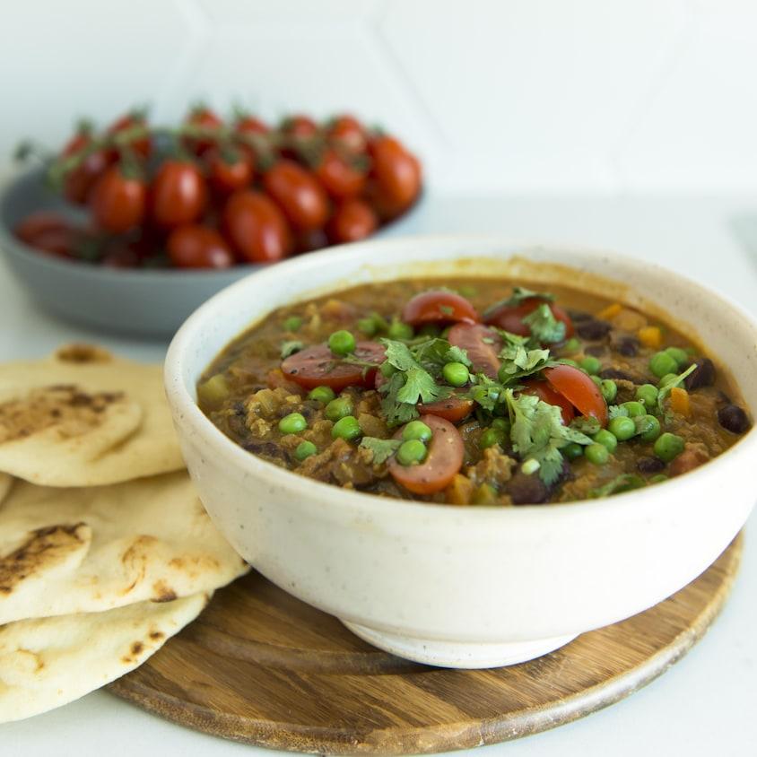 Un bol de chili avec des petits pois et de la coriandre.