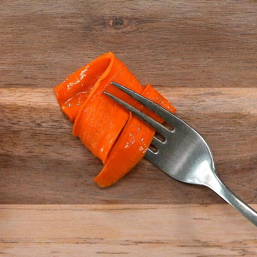 Une tranche de carotte confite enroulée sur une fourchette.