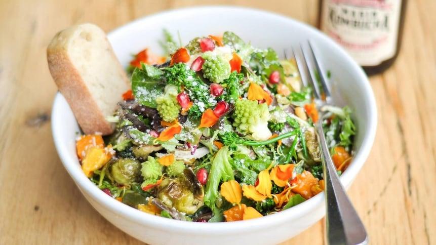 Un bol de salade colorée est servi sur une table en bois.
