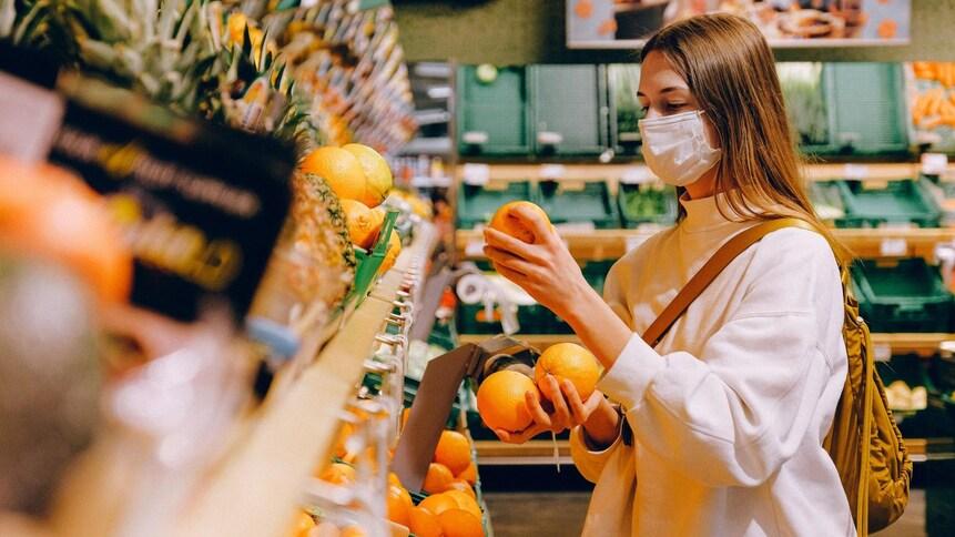 Une jeune femme masquée choisit des oranges au marché.