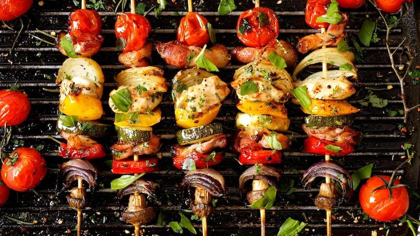 Des brochettes de légumes et de viande, sur lesquelles on a saupoudré des épices et des herbes, cuisent sur une grille de barbecue.