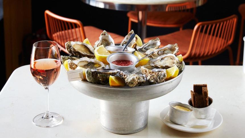 Un plateau d'huîtres ouvertes déposé sur une table, à côté d'un verre de vin rosé et d'une petite assiette de pain.