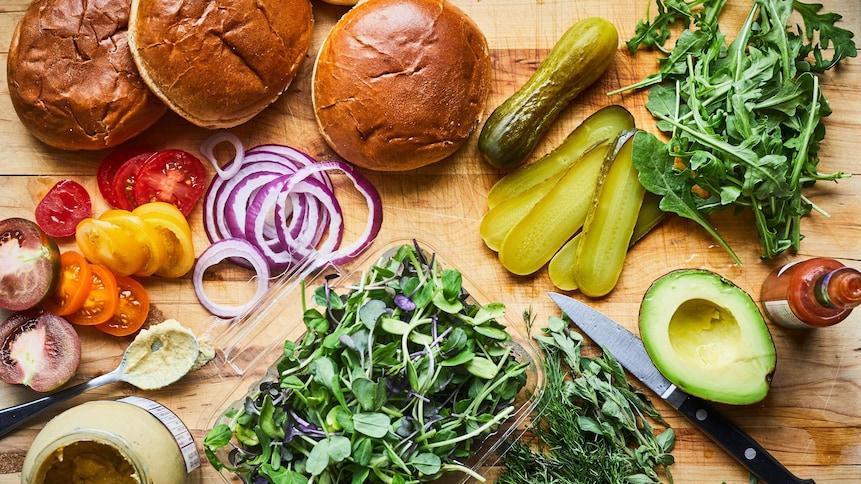 Sur un ilot de cuisine des pains à burgers ont été tranchés en deux, cinq tranches de cornichons, la moitié d'un avocat, des herbes fraîches et un pot de moutarde à Dijon y ont été aussi déposés.