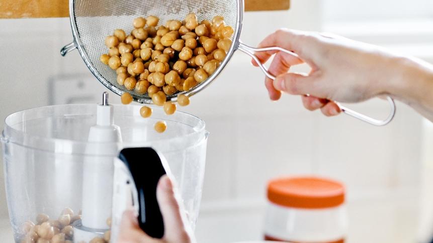 Une personne verse des pois chiches dans un robot culinaire.