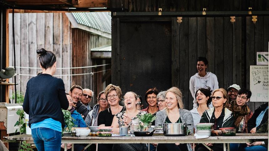 Une personne donne un atelier culinaire devant un groupe de gens assis derrière de longues tables en bois.