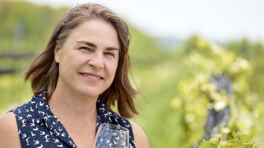 La vigneronne Ann Sperling dans son vignoble, un verre de vin blanc à la main.