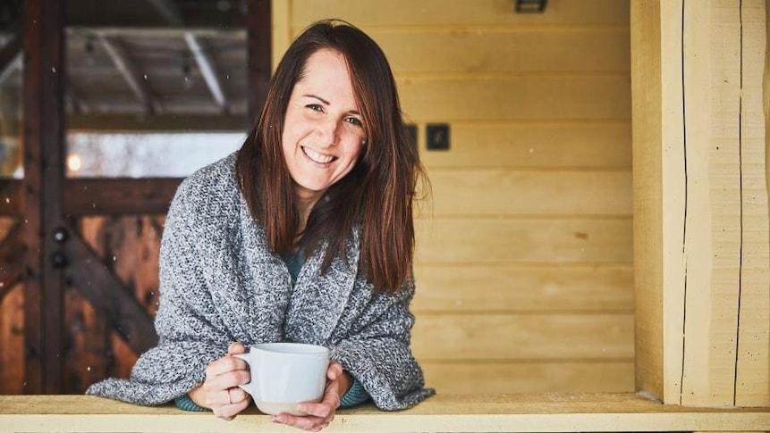 Geneviève O'Gleman tient une tasse entre ses mains et a un châle sur les épaules. Elle est sur une galerie en bois.