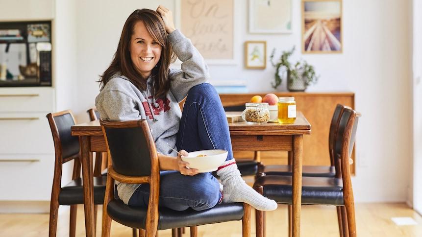 Geneviève O'Gleman assise sur une chaise de manière décontractée et tenant un bol à la main. Sur la table en arrière-plan, on voit du granola, du miel et des pommes.