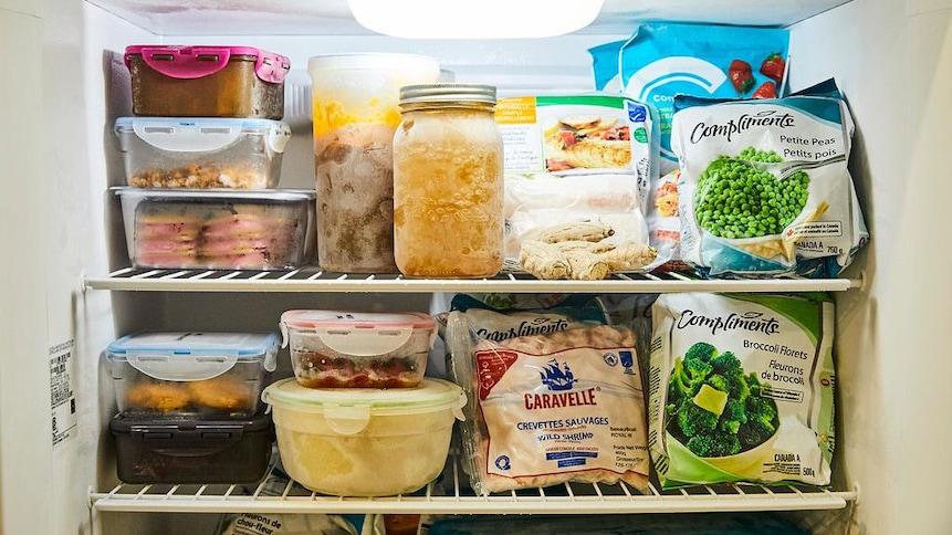 L'intérieur d'un congélateur avec divers aliments congelés.