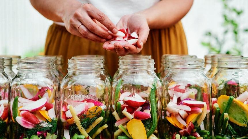 Femme qui remplit des pots de conserve en verre avec des légumes.