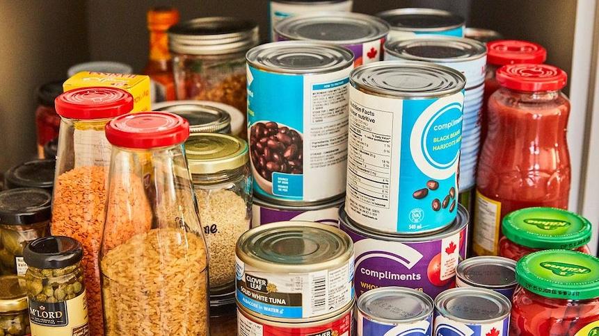 Dans le tiroir d'une armoire de cuisine plusieurs conserves de thon, de tomates en dé, de haricots noirs, de tomates coupées ont été placées.