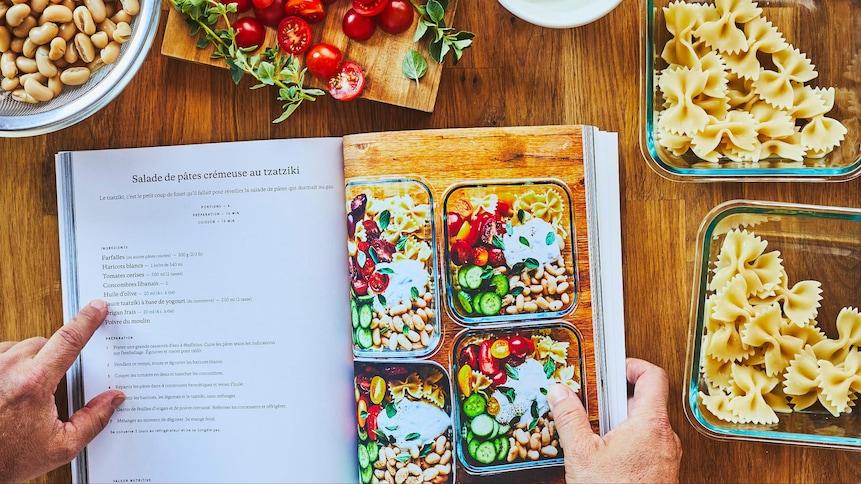 Un livre de recettes ouvert sur un plan de travail entouré de haricots blancs, de tomates cerise et de pâtes alimentaires.