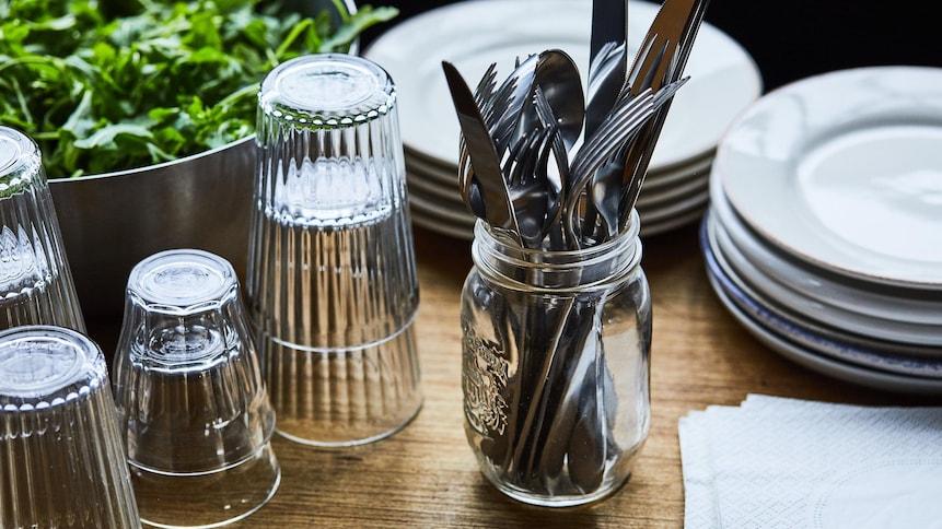 Piles de verres vides, piles d'assiettes blanches et pot mason contenant plusieurs ustensiles.