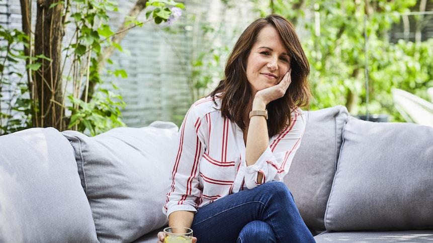 La nutritionniste Geneviève O'Gleman assise sur un canapé à l'extérieur avec un une eau citronnée à la main et de la verdure en arrière plan.