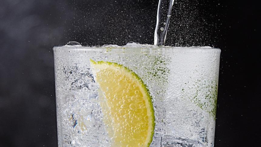 De l'eau pétillante versée dans un verre avec un quartier de lime.