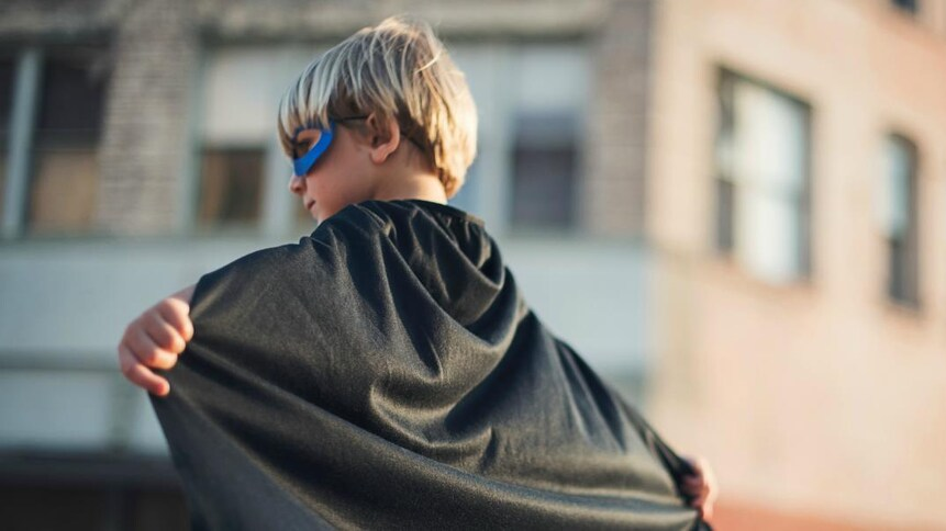 Garçon en costume de super héros.