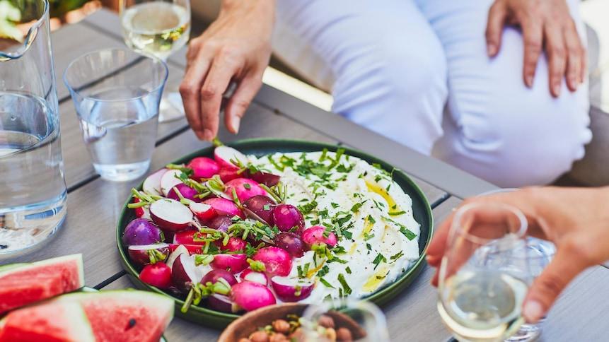 Assiette de ricotta fouettée avec des radis et du persil.