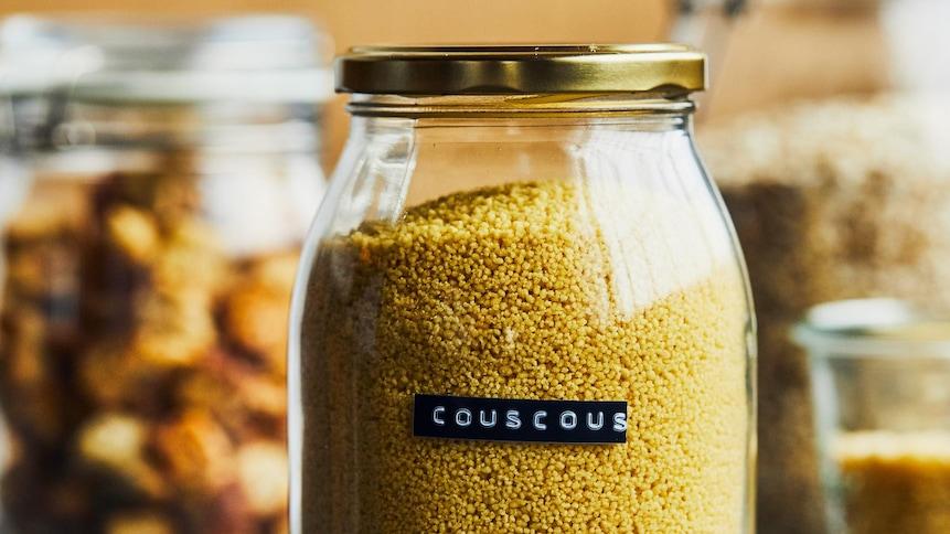 Pot de verre avec un couvercle de métal contenant du couscous.