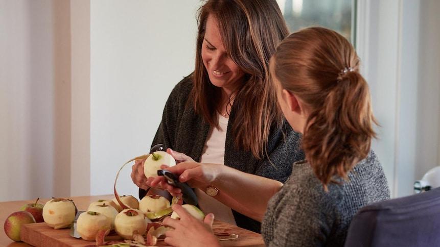 Geneviève et sa fille Maude, sont assise à la table de cuisine et elles enlèvent la pelure des pomes.