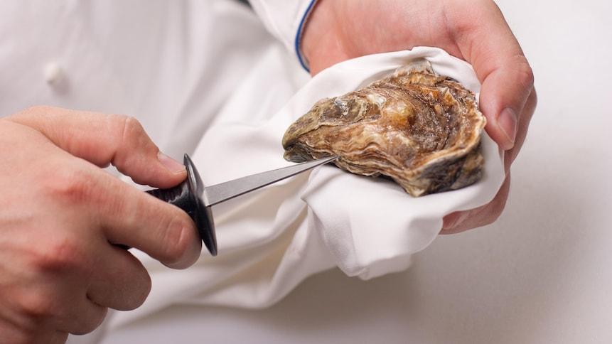 Un chef qui ouvre une huitre fraîche avec un couteau.