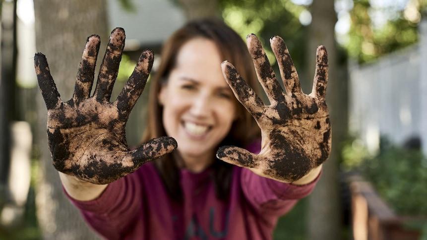 Geneviève O'Gleman montre ses mains pleines de terre à jardin.