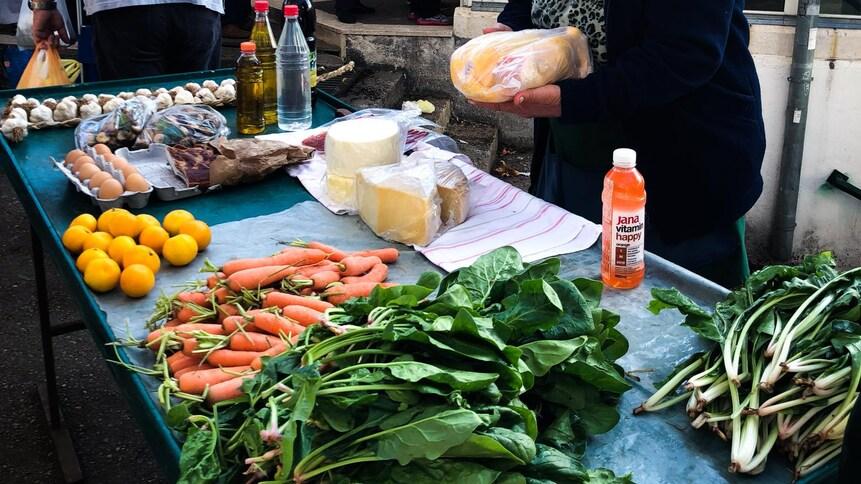 Femme qui vend des légumes dans un marché croate.