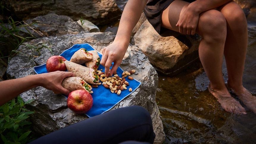 Sandwichs roulés dans des tortillas de blé avec un mélange de noix et deux pommes rouges.