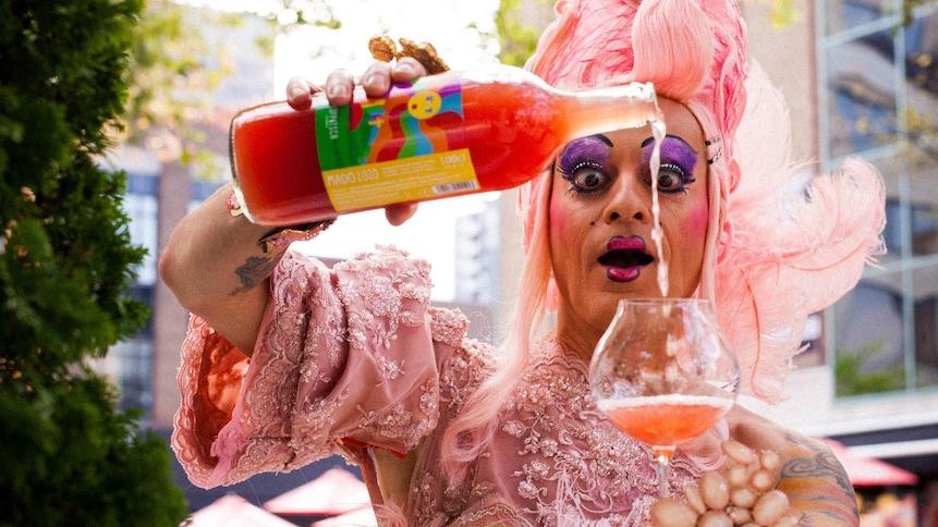 Mado Lamotte se verse un verre de Mado, un vin d'une couleur rose orangé.