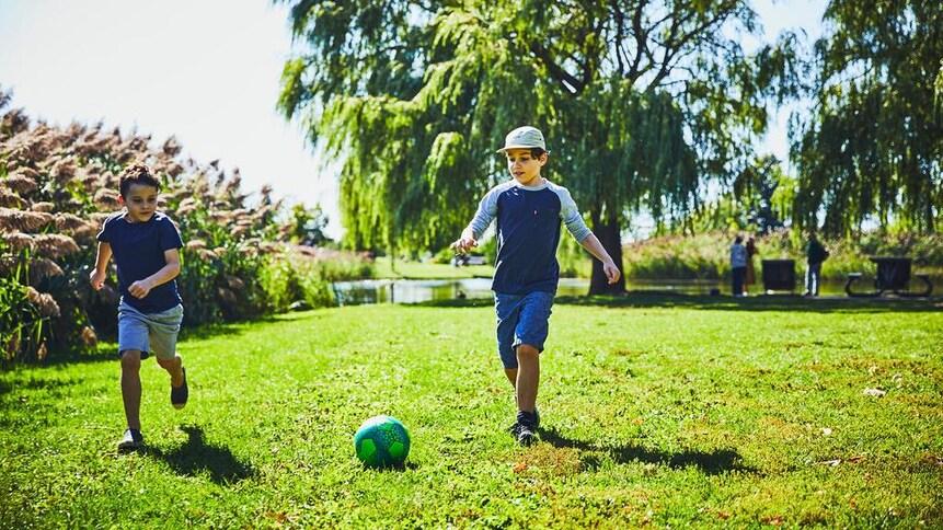 Deux enfants qui jouent avec un ballon de soccer dehors.