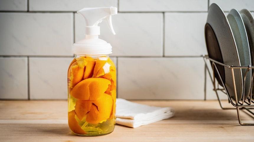Bouteille vaporisateur transparente contenant du vinaigre et des écorces d'oranges.