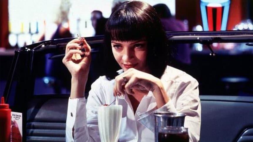 Une femme dégustant un milk-shake à la vanille avec une cerise.