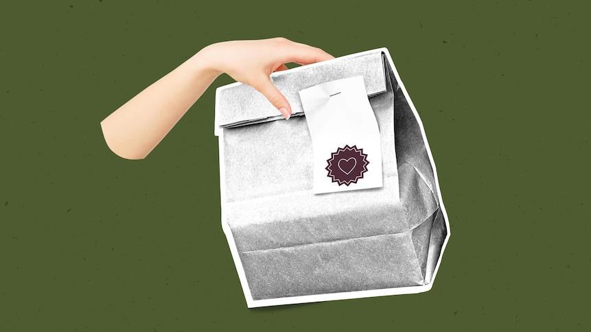 Le bras d'une femme qui tient un repas dans un sac de papier.